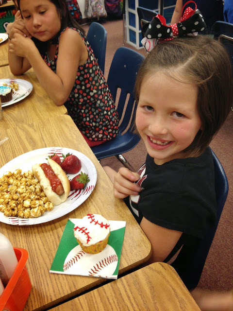 Little girl smiling with hotdog, strawberries, cracker jacks and cupcake at a post testing party