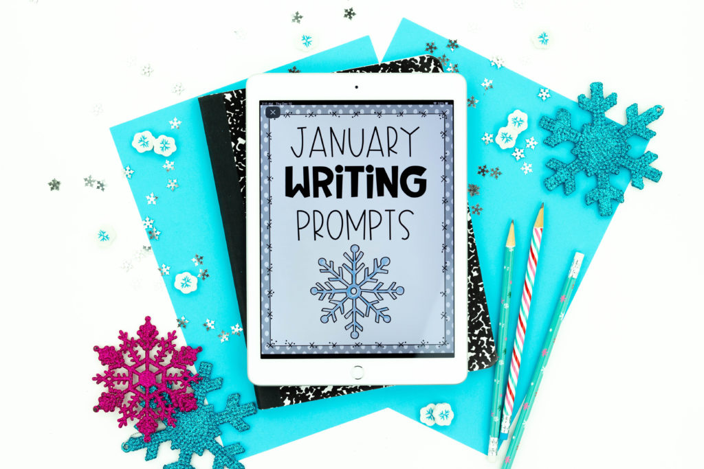Blue background paper, composition book, and snowflakes with January Writing Prompts on iPad