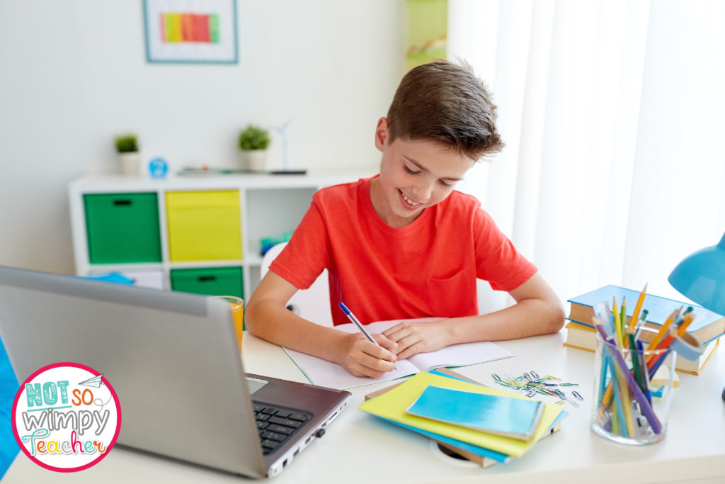 Boy in orange shirt with laptop, notebooks, pencils and books doing remote learning
