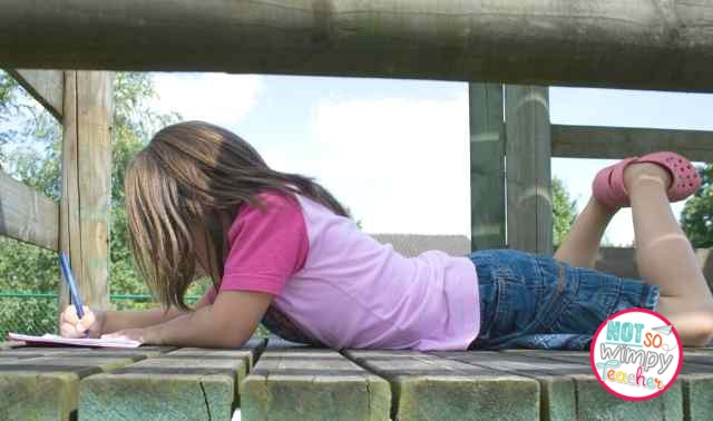 Girl in pink t-shirt and denim skirt lying on her belly outside writing