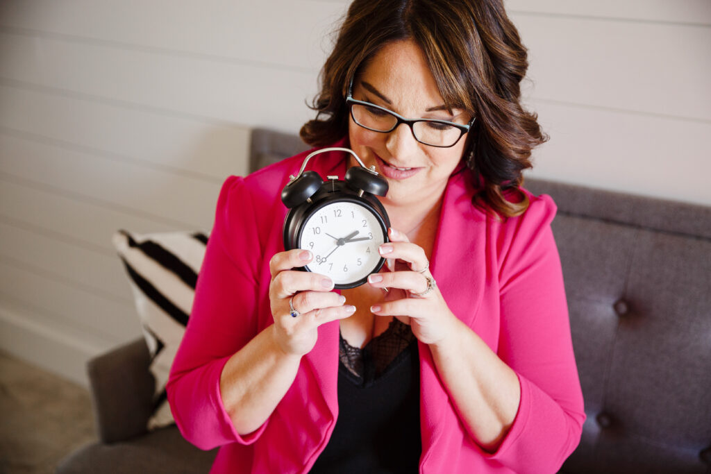 Woman in pink jacket with brown hair and glasses holding an alarm clock to time transitions