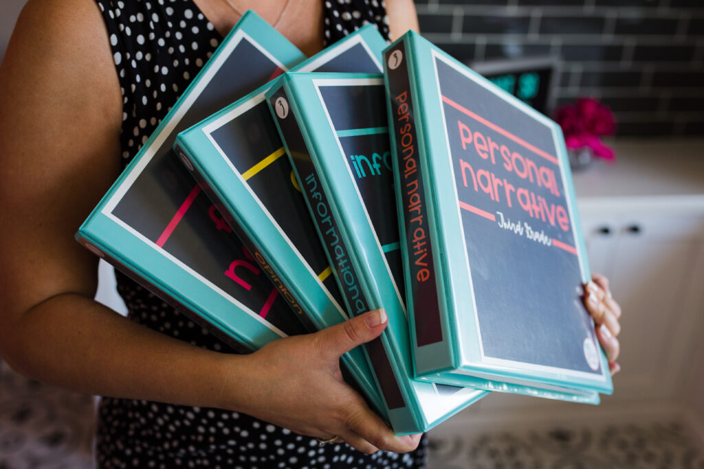 Woman holding binders with four main writing units: personal narrative, informational report, opinion essay, and fiction
