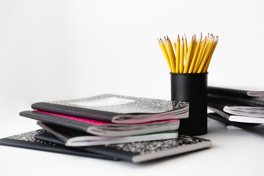 Pile of composition notebooks and cup with yellow pencils