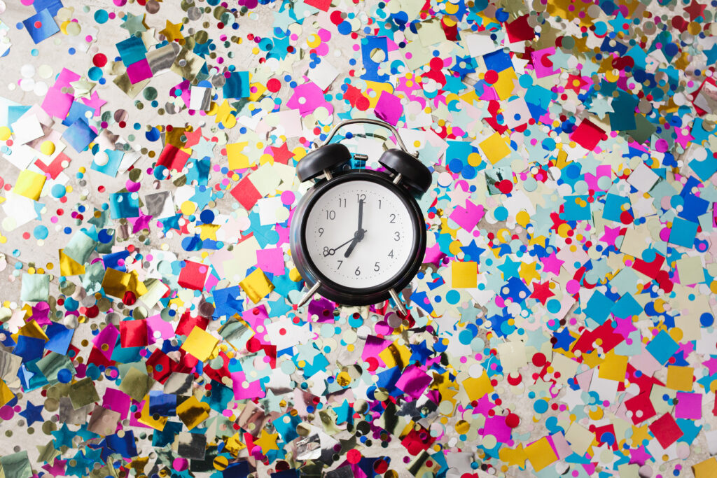 Old fashioned clock in the middle of confetti  showing 7 pm, the time the Writing Masterclass registration closes on July 1st